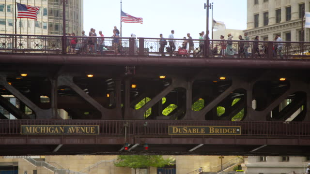 ms pan people walking on michigan avenue bridge, national flags waving on bridge, buildings in background / chicago, illinois, united states - dusable bridge stock videos & royalty-free footage