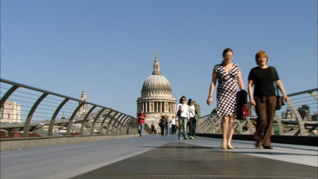 MS people walking on Millenium Bridge, St. Paul's Cathedral in background, London, England