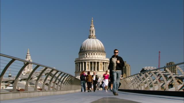 ms people walking on millenium bridge, st. paul's cathedral in background, london, england - london millennium footbridge stock videos and b-roll footage