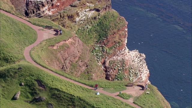 aerial ms people walking on mountain near ocean / heligoland, schleswig-holstein, germany - helgoland stock videos & royalty-free footage