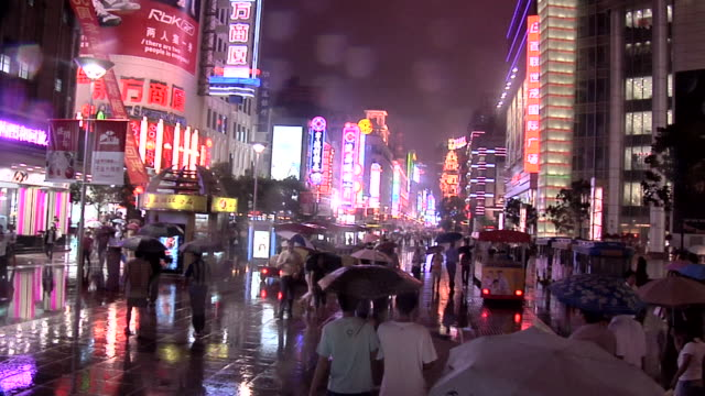 ws people walking on nanjing road east on rainy night/ shanghai, china - nanjing stock-videos und b-roll-filmmaterial