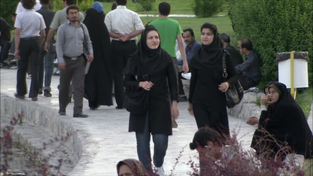 ms pan people walking on path in park by zayandeh river, isfahan, iran - モデスト・ファッション点の映像素材/bロール