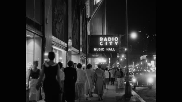 people walking on pavement outside radio city music hall at night, rockefeller center, midtown manhattan, new york city, new york state, usa - radio city music hall stock videos & royalty-free footage
