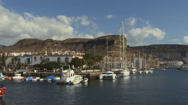 ws pan people walking on pier at marina/ puerto de mogan, grand canary, canary islands - grand canary stock videos and b-roll footage