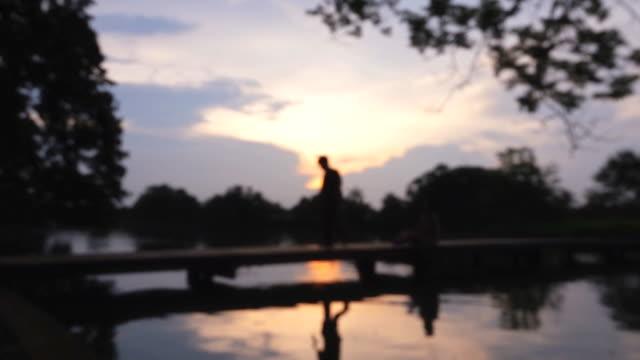 people walking on pier at sunset, slow motion defocused - footbridge stock videos & royalty-free footage