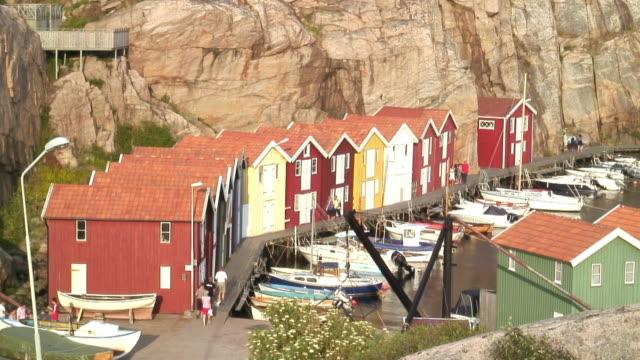 WS HA People walking on pier by boat huts / Smogen, Tjorn Island, Bohuslan, Sweden