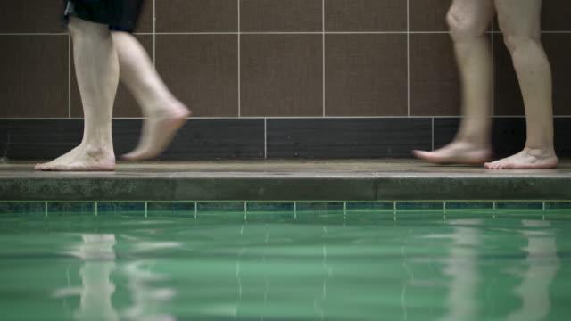 stockvideo's en b-roll-footage met people walking on poolside, low section. - binnenbad