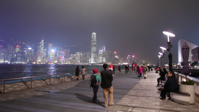 ws people walking on promenade at victoria harbour at night, city skyline in background / hong kong, china - promenade stock videos & royalty-free footage