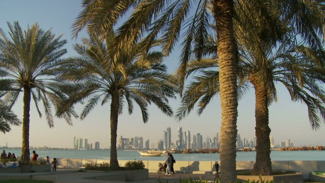 ws people walking on promenade with palm trees in foreground, financial district skyscrapers across bay in distance / doha, qatar - doha stock videos & royalty-free footage