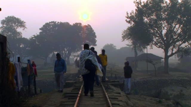vidéos et rushes de people walking on railway track - châle