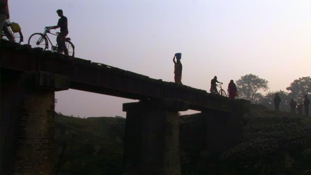 people walking on railway track - dhoti video stock e b–roll