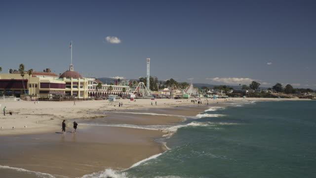 people walking on resort beach near amusement park / santa cruz, california, united states - カリフォルニア州サンタクルーズ点の映像素材/bロール