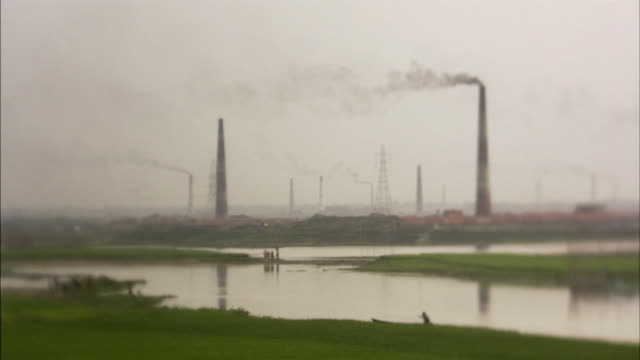 vídeos de stock, filmes e b-roll de ws, r/f, selective focus, people walking on riverbank with smoke stacks in background, bangladesh - bangladesh