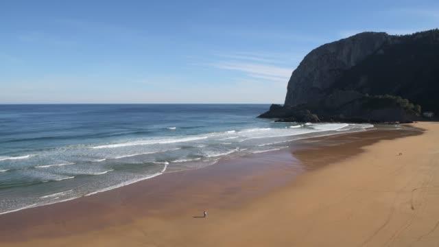 People walking on sand beach. Playa de Laga is a famous sand beach in the Spanish Basque Country near Bermeo.