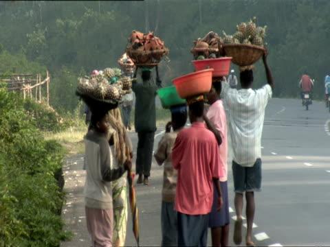 ws people walking on side of road carrying baskets and bundles on their heads / kigali, rwanda - キガリ点の映像素材/bロール