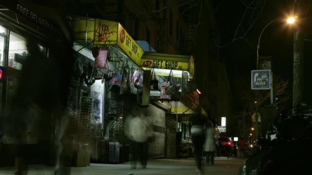 vídeos de stock, filmes e b-roll de t/l ws people walking on sidewalk along closed storefronts at night, new york city, new york, usa - escrita ocidental