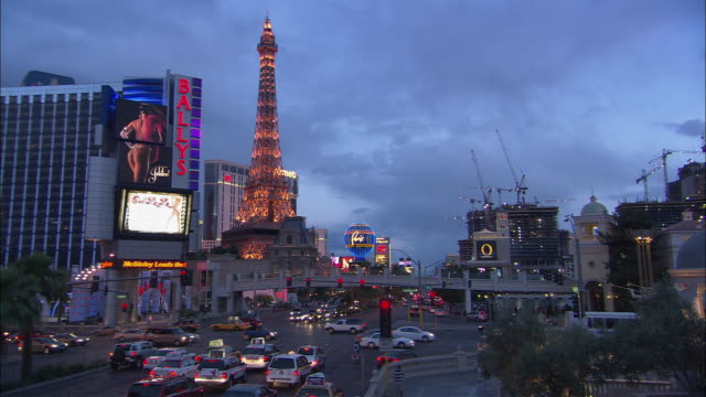 ha ws people walking on sidewalk at intersection as traffic passes by eiffel tower replica at paris hotel at dusk/ las vegas, nevada - replica della torre eiffel video stock e b–roll