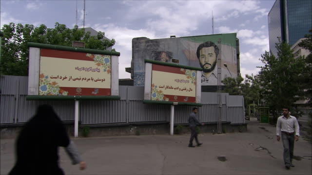 ws people walking on sidewalk, billboards in background, iran - modest clothing stock videos & royalty-free footage