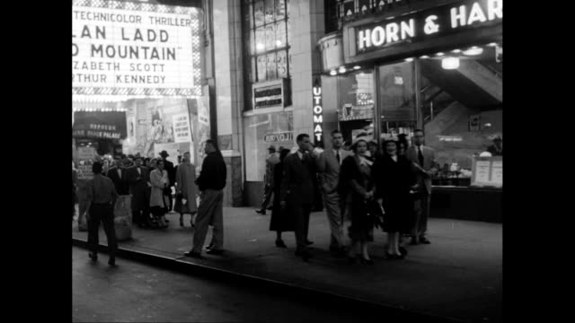 vídeos de stock e filmes b-roll de ms pov pov people walking on sidewalk in times square, passing by theater and automat restaurant at night / united states - 1950