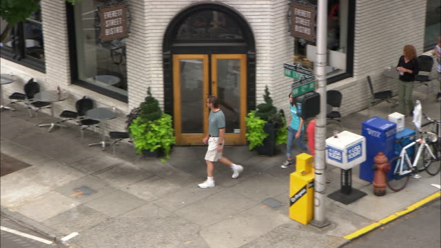 WS HA PAN People walking on sidewalk past bistro in Pearl District / Portland, Oregon, USA