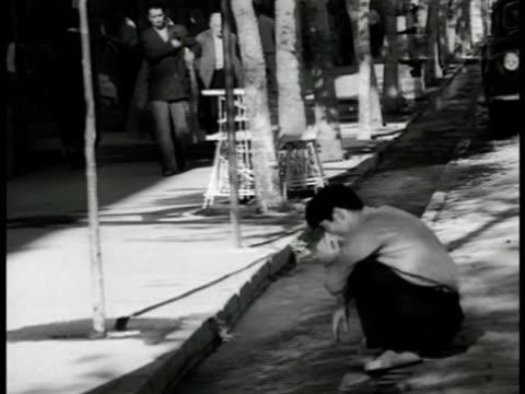 people walking on sidewalks w/ open gutters fg iranian man washing face in open gutter water open air bazaar people buying / vendors selling... - 1951 stock videos & royalty-free footage