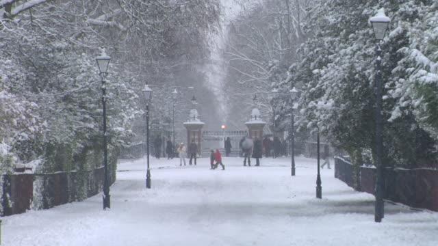 vídeos de stock e filmes b-roll de ws people walking on snowy street in front of park gate / victoria park, london - floco de neve