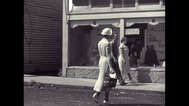 MS PAN People walking on street, entering shop in small town / United States