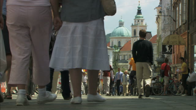 MS People walking on street in old town, Saint Nicholas' Cathedral in background / Ljubljana, Slovenia