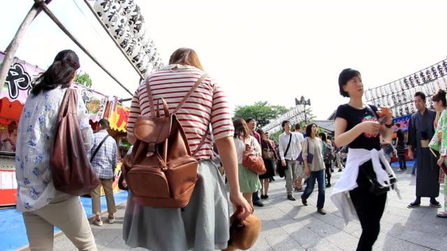 vídeos de stock, filmes e b-roll de ms pov people walking on street near senso ji temple / asakusa, tokyo, japan - templo asakusa kannon