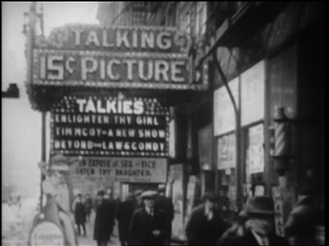 vidéos et rushes de b/w 1934 people walking on street under flashing marqee talking 15c picture talkies / chicago - 1934