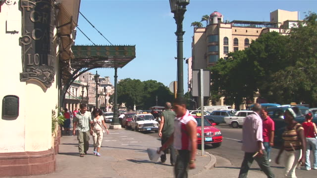 vídeos de stock, filmes e b-roll de ws people walking on streets of havana with traffic / havana city, havana, cuba - escrita ocidental