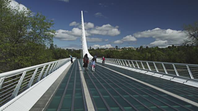 vídeos de stock e filmes b-roll de ws people walking on sundial bridge at turtle bay redding / redding, california, usa  - ponte com armação cantilever