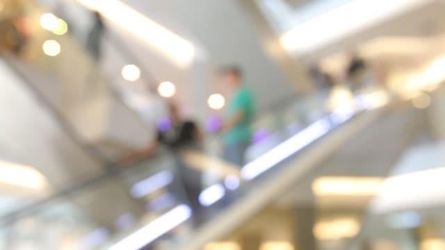 vídeos de stock, filmes e b-roll de povos que andam na escada rolante em uma cena totalmente borrada na alameda de compra - liquidação evento comercial