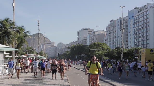 people walking on the rio de janeiro sidewalk and bike line during sunday - rio de janeiro stock videos & royalty-free footage