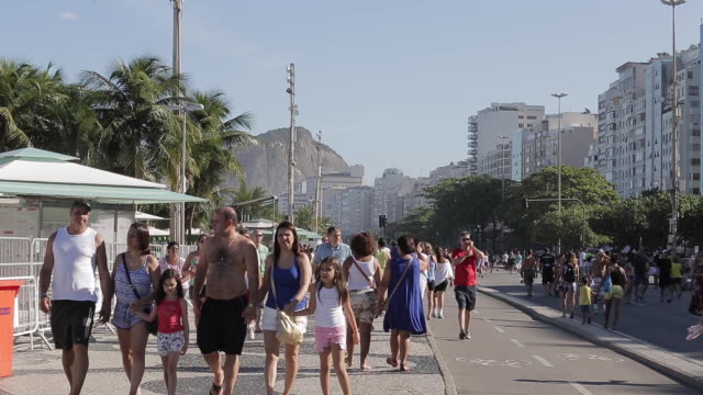 people walking on the rio de janeiro sidewalk and bike line during sunday - urban road stock videos & royalty-free footage