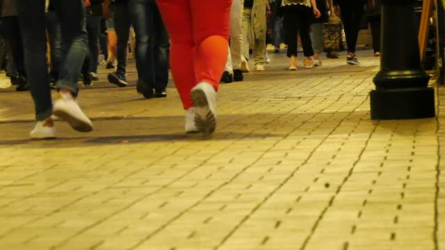 menschen, die nach sonnenuntergang auf der straße spazieren gehen - menschliche gliedmaßen stock-videos und b-roll-filmmaterial