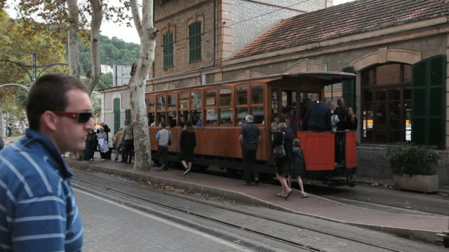 WS People walking on tram platform with Tram standing by at Puerto Soller near Soller / Mallorca, Balearic Islands, Spain