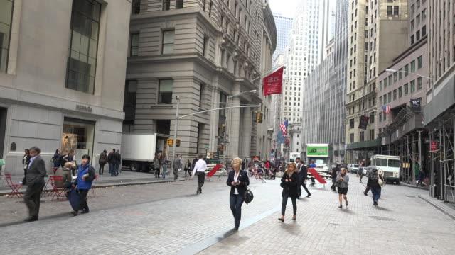 people walking on wall street in new york city - international landmark stock videos & royalty-free footage