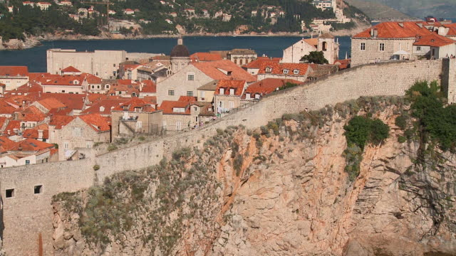 ws pan people walking on wall surrounding the city/ dubrovnik, dalmatia - surrounding wall stock-videos und b-roll-filmmaterial
