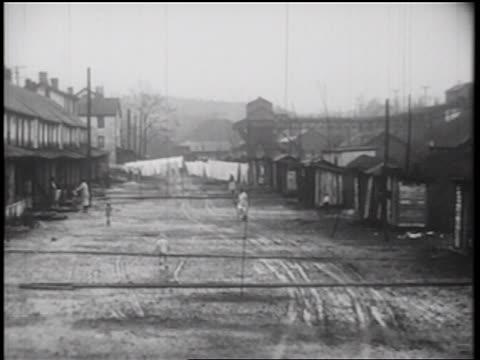 stockvideo's en b-roll-footage met b/w 1939 people walking on wide muddy street past shacks in shantytown / documentary - grote depressie nieuwsevenement