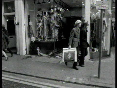 people walking out of shop carrying bags of shopping on carnaby street during swinging 60's carnaby street sign visible - swinging stock videos & royalty-free footage