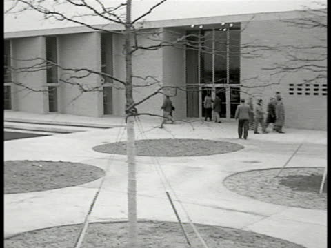 People walking outside LPRA Building modern office complex Architect Alfred Levitt working at desk in office