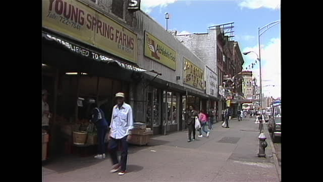 people walking outside of a food market in new york city's chinatown in the 1980s. - chinatown stock videos & royalty-free footage