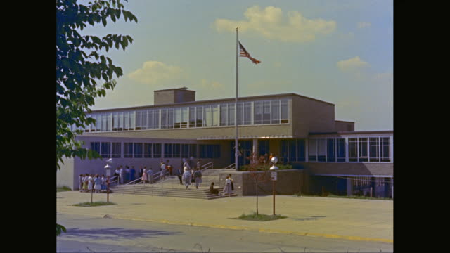 vidéos et rushes de ws people walking outside of birmingham high school / birmingham, michigan, united states - 1960