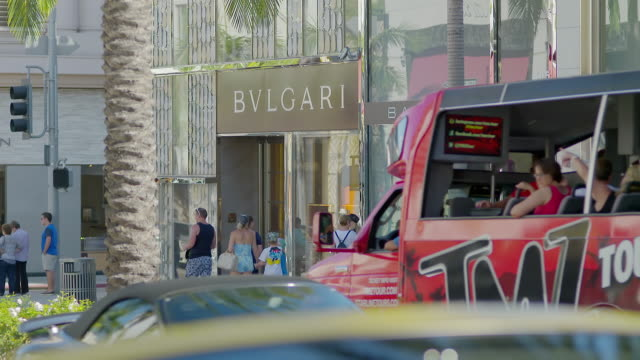 WS TD People walking outside of shop, land vehicles moving in foreground / Rodeo Drive, Beverly Hills, Los Angeles County, California, United States