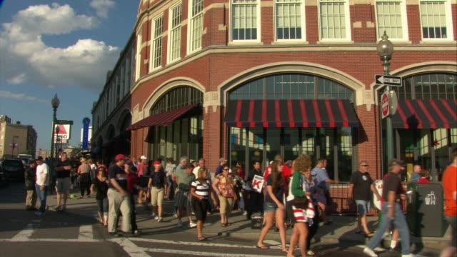 ws pan people walking outside stadium's main entrance before game in fenway park / boston, massachusetts, usa - baseballmannschaft stock-videos und b-roll-filmmaterial