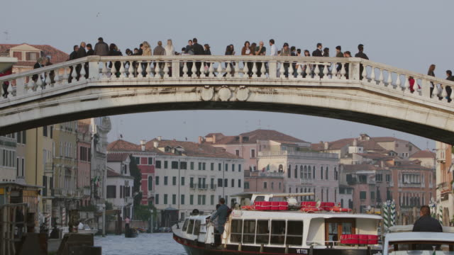 WS People walking over a canal bridge in Venice, boat passing under same bridge / Venice, Italy