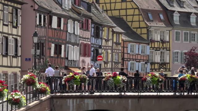 People walking over Rue des Ecoles Bridge over river Lauch in La Petite Venise