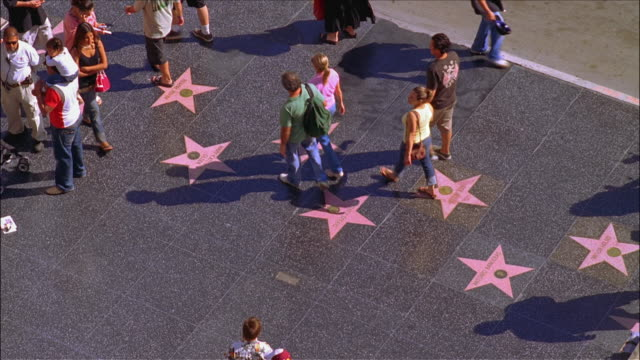 people walking over stars on hollywood walk of fame / hollywood, los angeles, california - ウォークオブフェーム点の映像素材/bロール