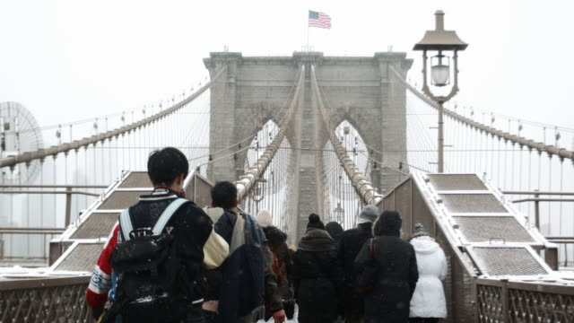 vidéos et rushes de people walking over the brooklyn bridge in a blizzard - pont de brooklyn